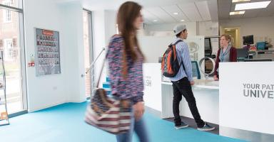 A student walking inside a Bell building.