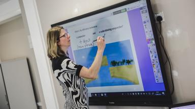Teacher at interactive whiteboard