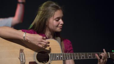 Performing arts student playing the guitar at Wellington College