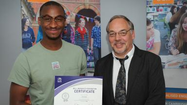 Kebe receiving his certificate from Ian Chitty